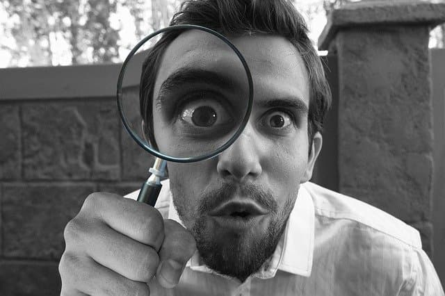Man looking through magnifying glas for evidence