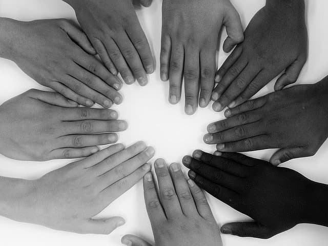 8 hands of people on a table, symbolizing shared responsibility